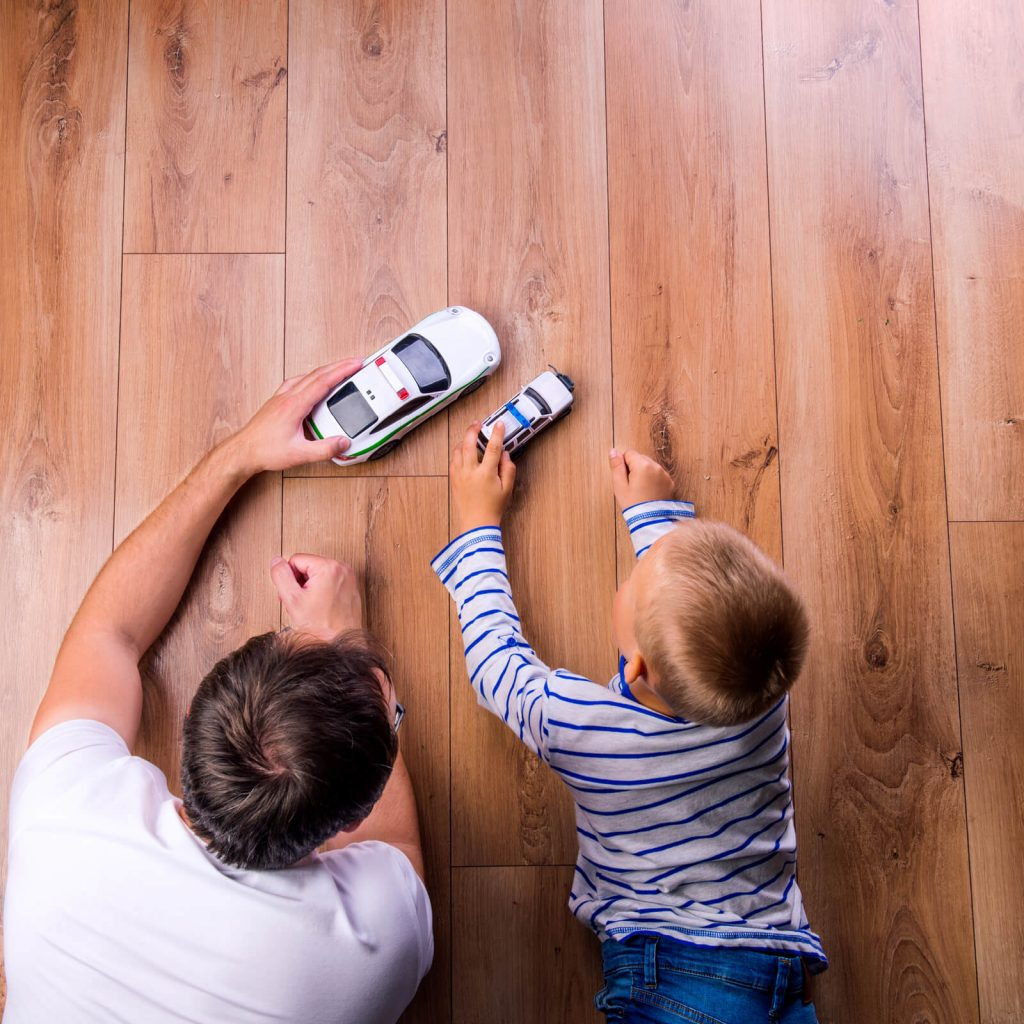 Father with kid playing with toycar | Assured Flooring